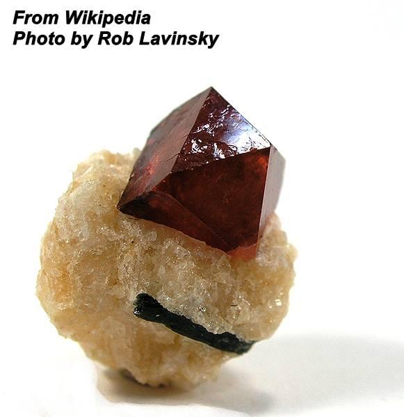 """זירקון אדומה על מצע סלע בהיר. נלקח ברשות מ""""ויקיפדיה"""" From Wikipedia Commons Photo by: Rob Lavinsky"""