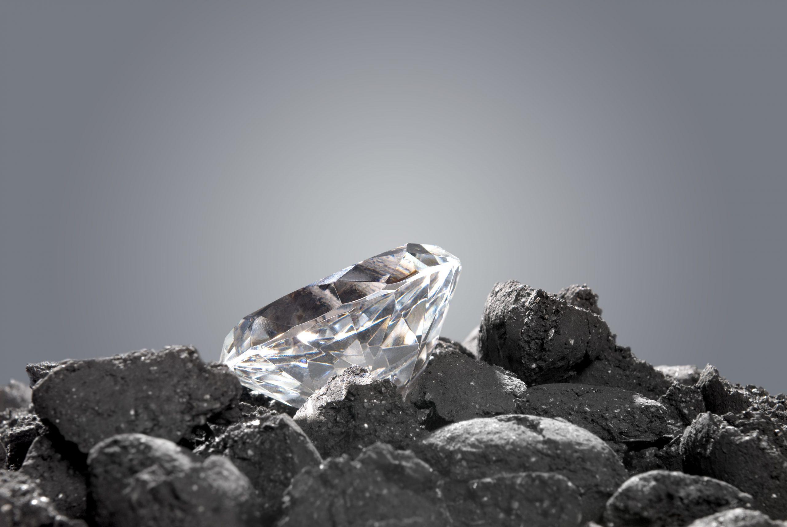"""יהלום מלוטש על ערימה של גושי פחם, המקור ממנו נוצר. התמונה נלקחה ממאגר התמונות """"דפוזיט""""."""