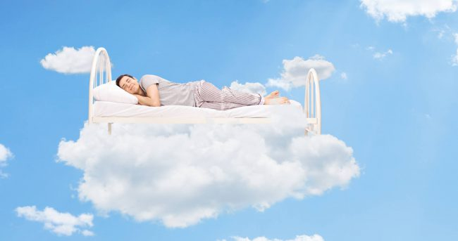 Man sleeping on a bed in the clouds high up in the sky